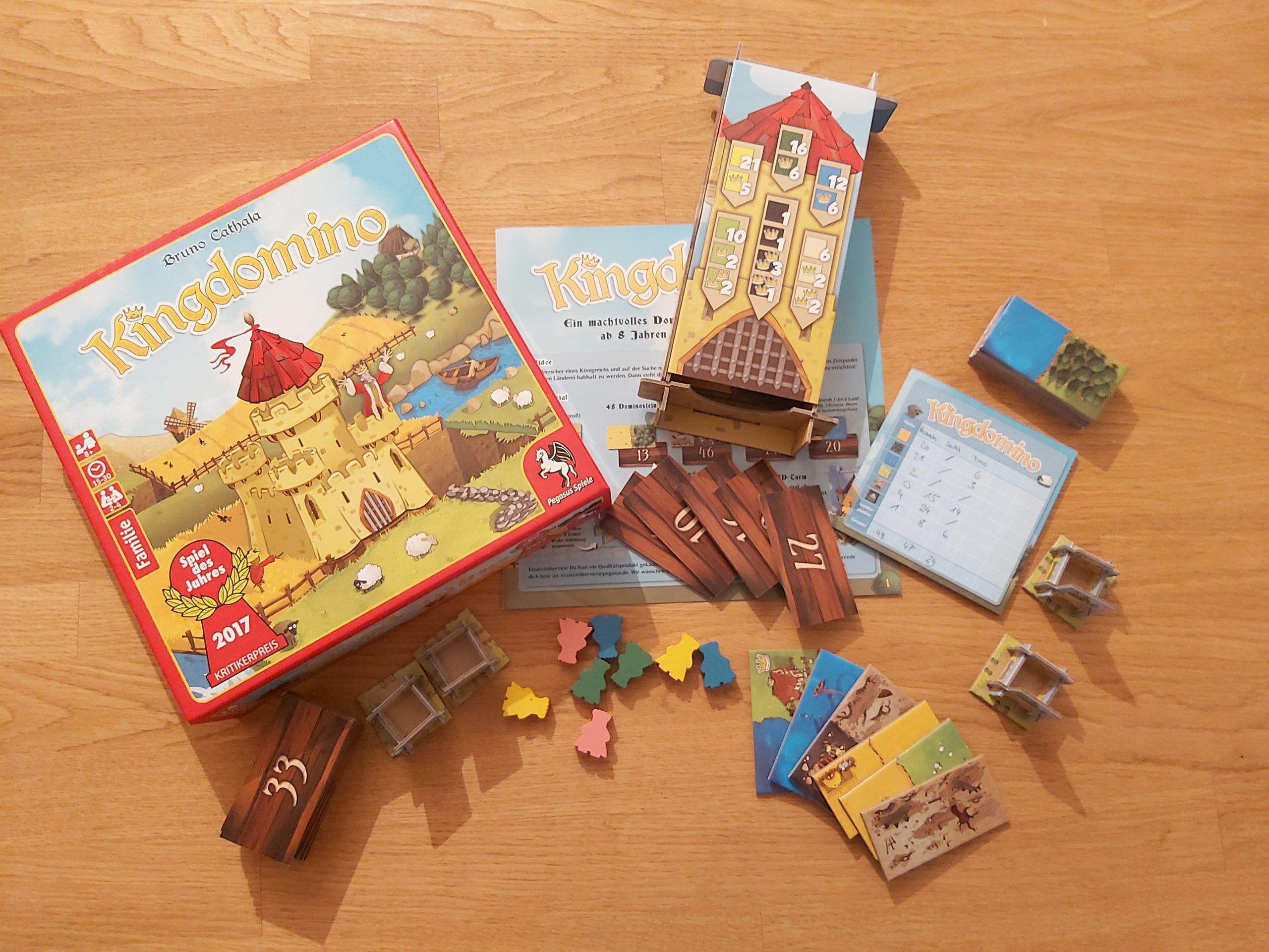 Zu sehen ist das Spiel Kingdomino mit dem gesamten Spielmaterial.
