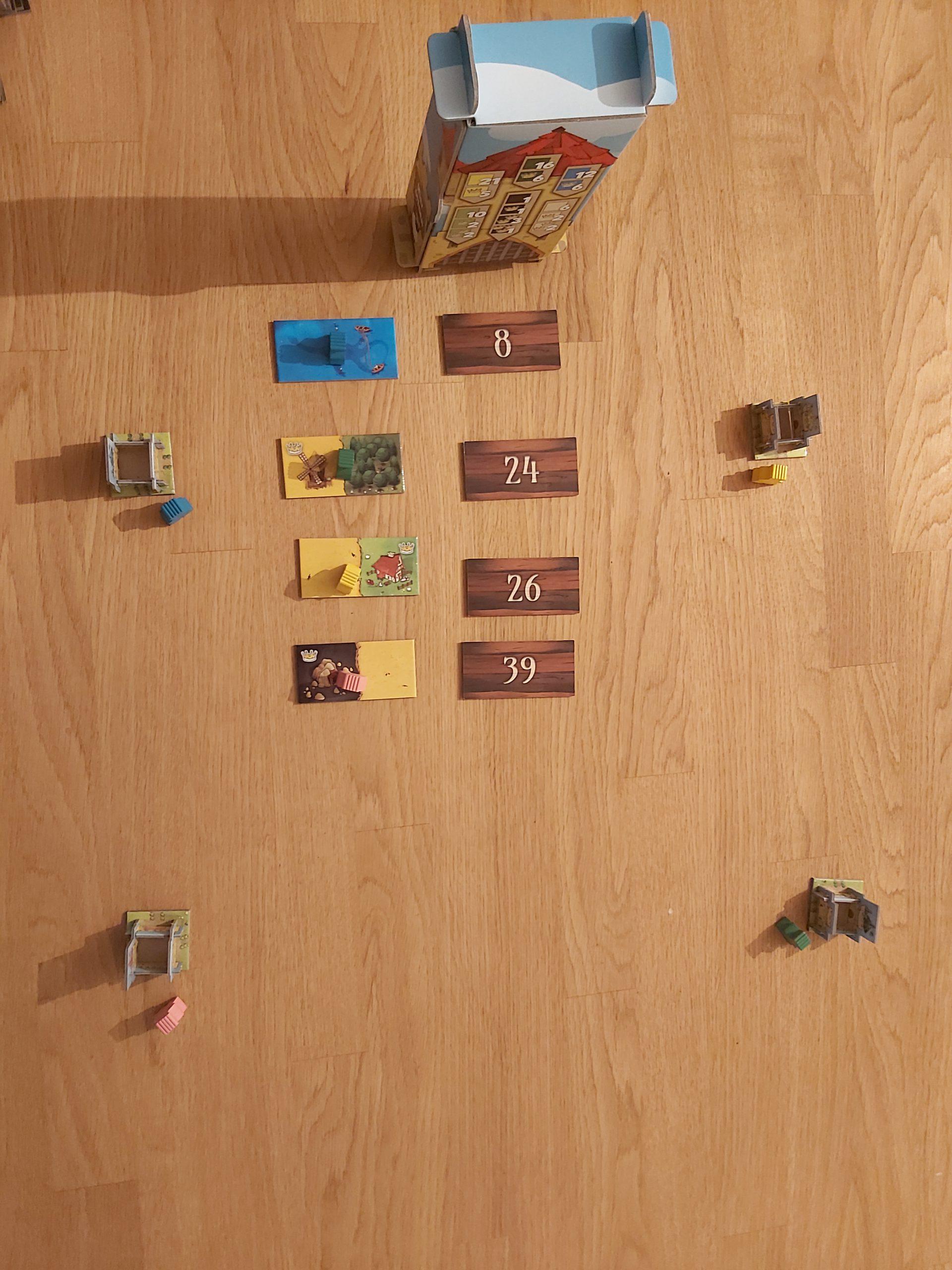 Zu sehen ist der Spielaufbau von Kingdomino für 4 Spielende