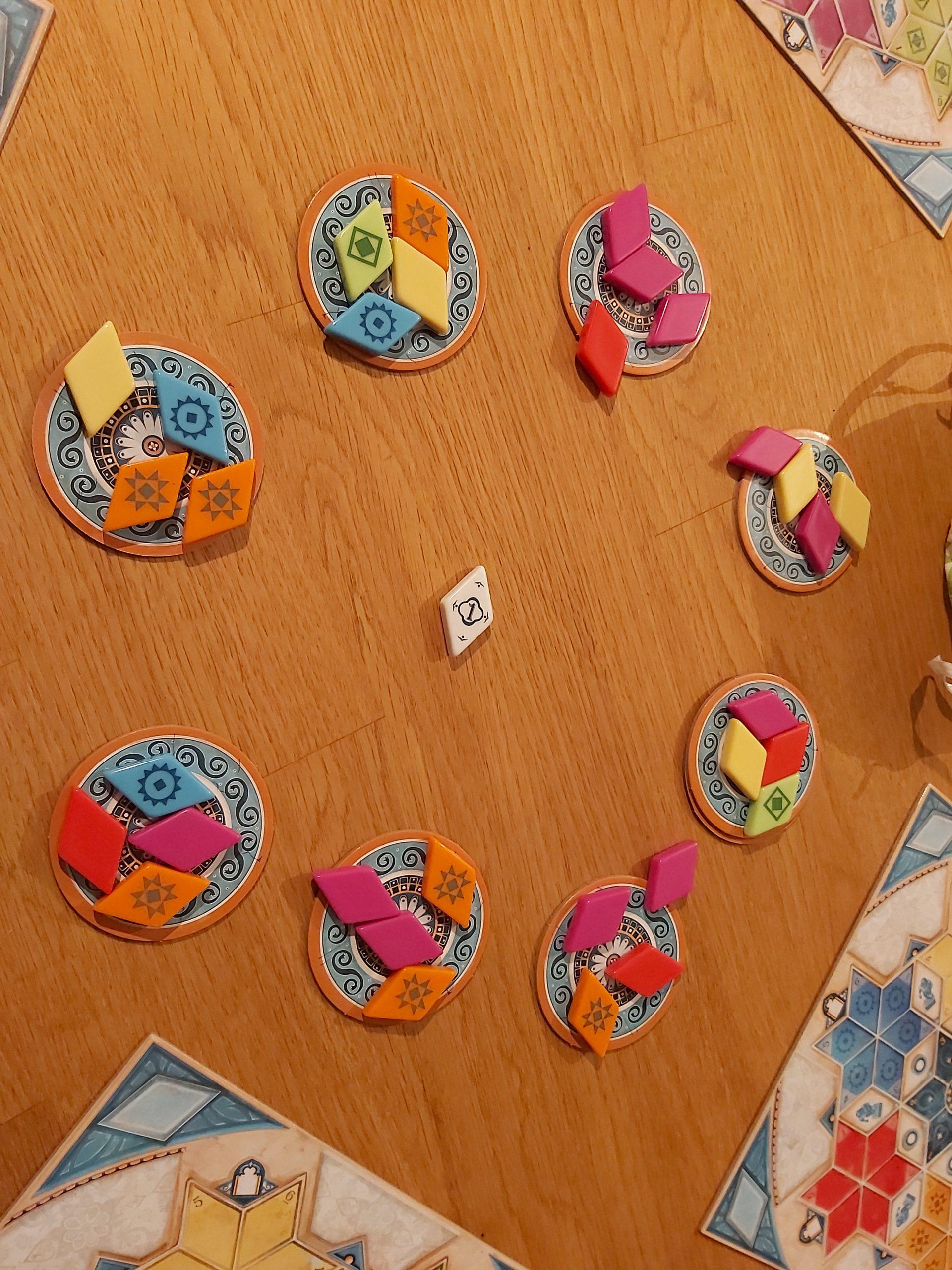 Zu sehen sind die Manufakturplättchen von Azul, auf denen Fliesen liegen.