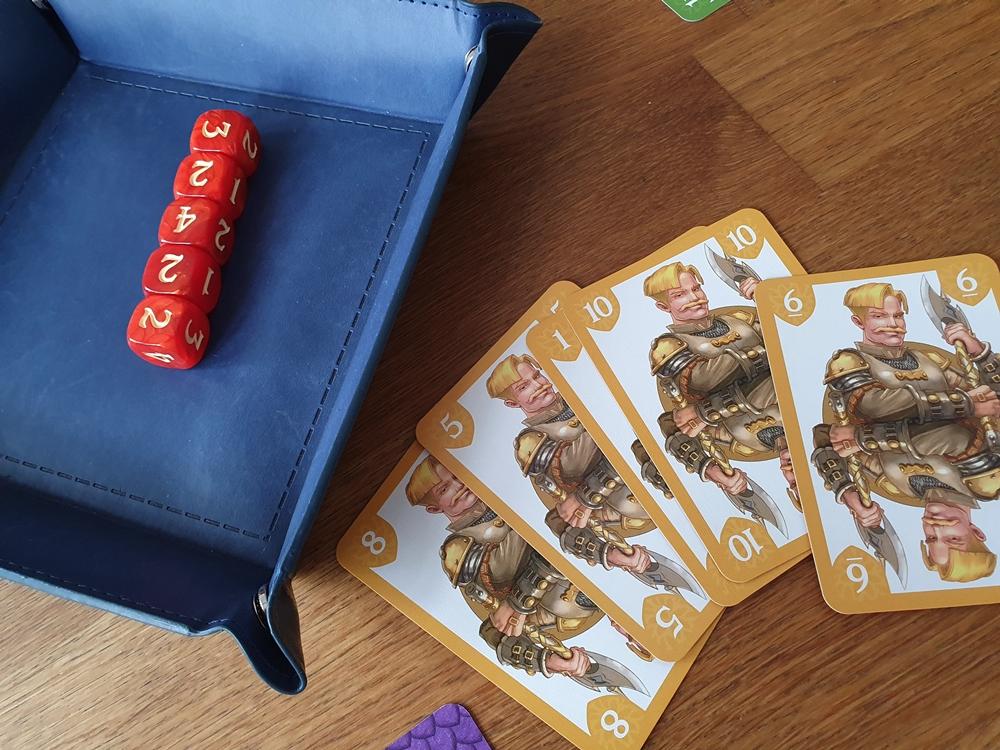 Eine Reihe von gelben Karten, Würfel auf einem Würfelteller