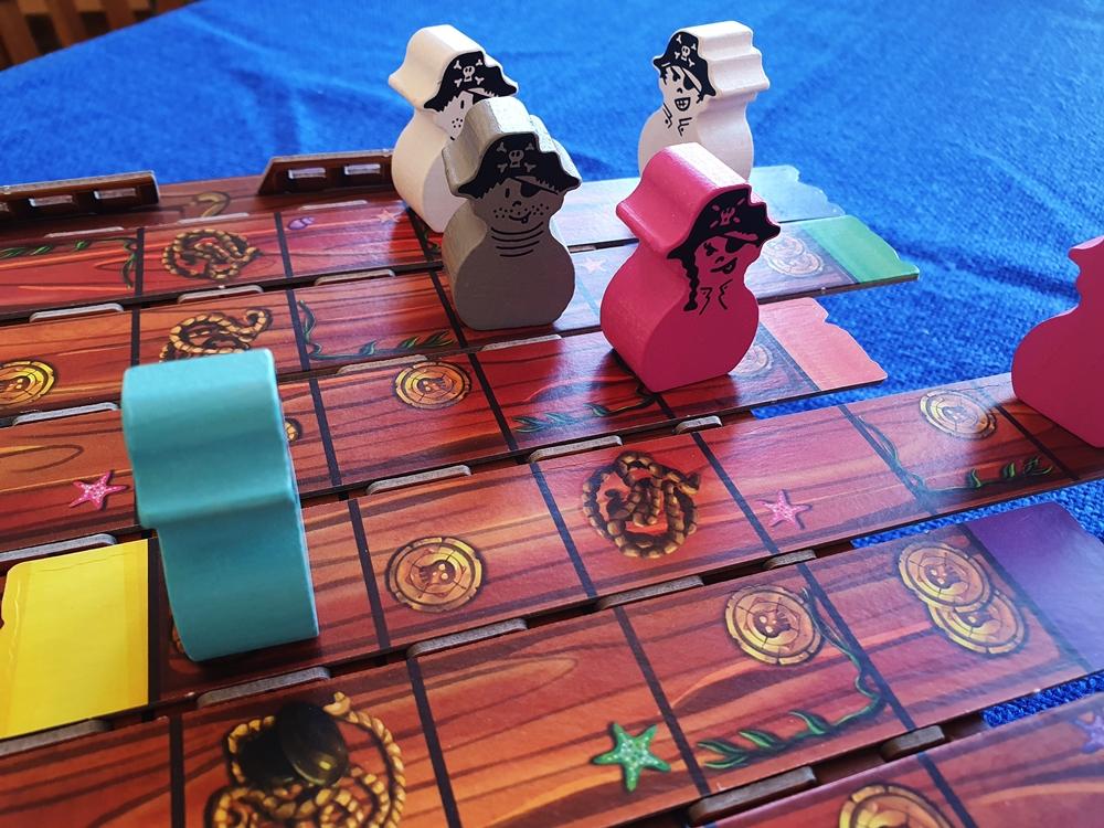 Piratenfiguren aus Holz sind auf dem Schiffsdeck verteilt