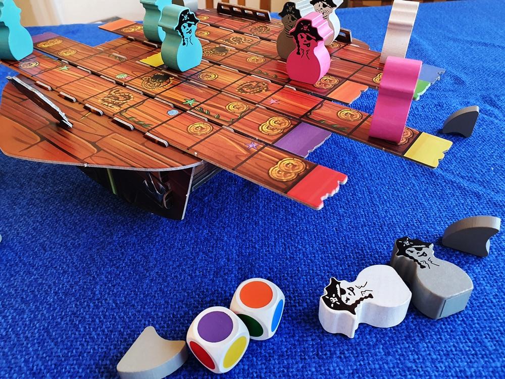 Das Spielschiff, zwei heruntergefallene Piratenfiguren, zwei Farbwürfel