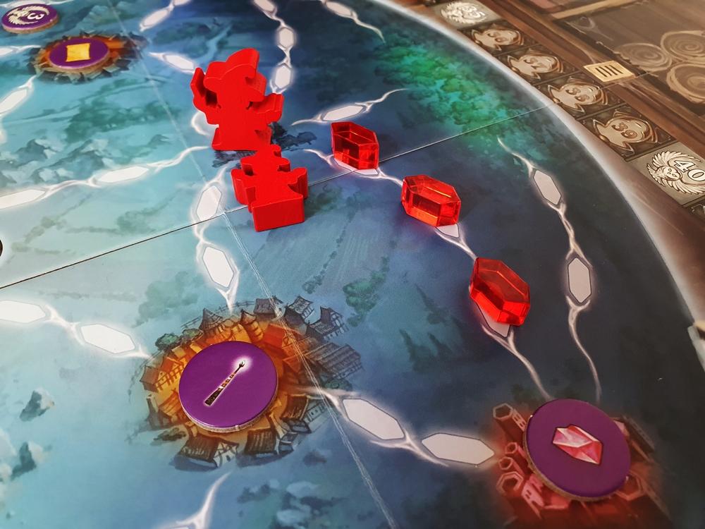 Teil des Spielfeldes: eine rote Hexe auf ihrem Startfeld, eine kleine liegend und ein erster Weg mit Leuchtsteinen markiert.