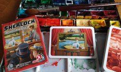 Spielschachtel und Inhalt, zur Dekoration ein Farbkasten und ein Pinsel